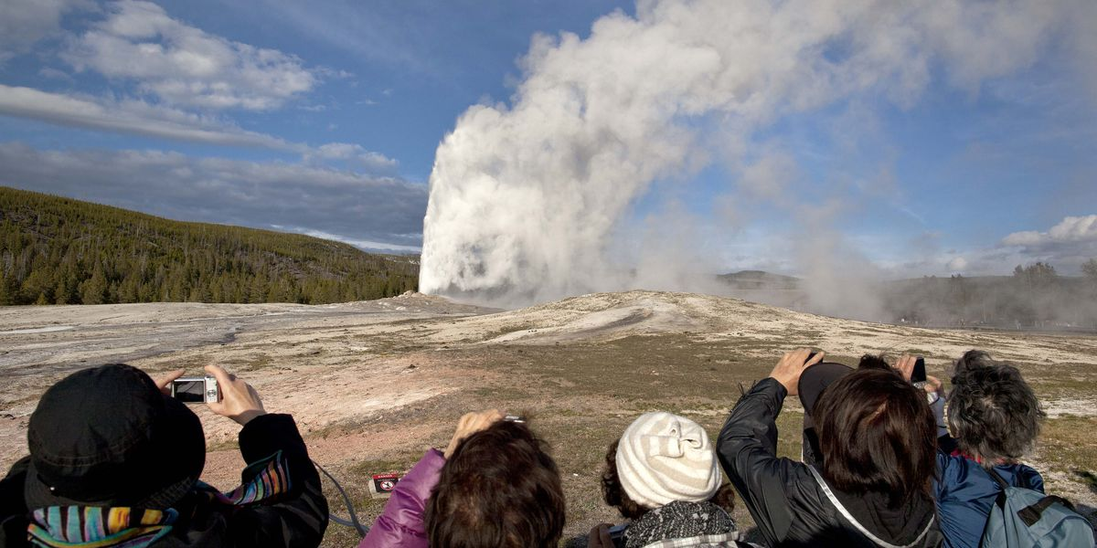 Tourist walks to edge of, and looks into, Old Faithful in Yellowstone National Park
