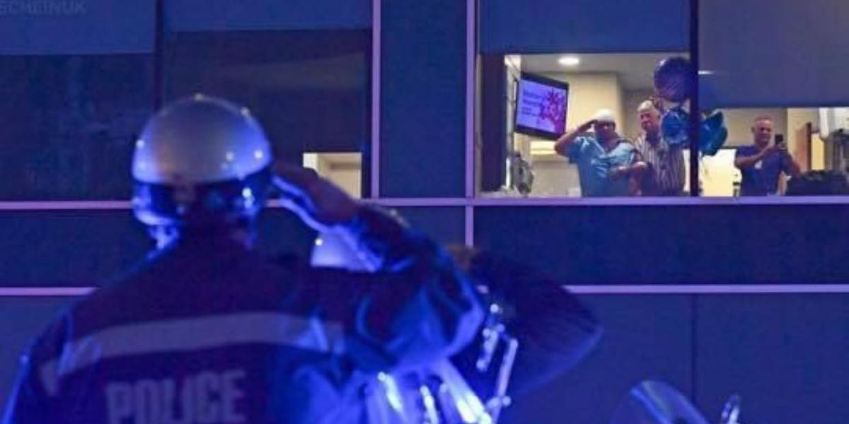 Officers salute Cpl. Maglone outside of hospital