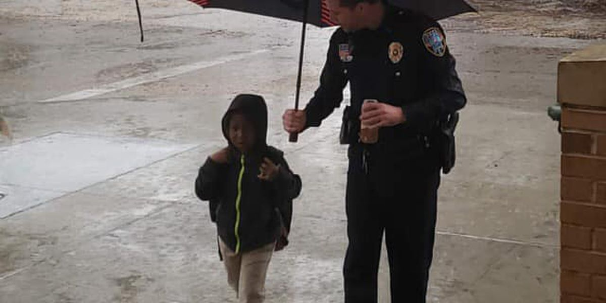 Slidell police officer shares umbrella with child walking to class